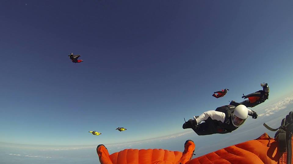 Paul Owen flying on his back in an orange wingsuit.