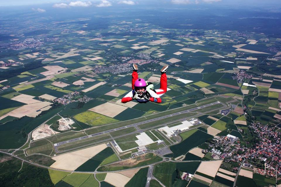 Chiara flying belly to earth with a town in the background.