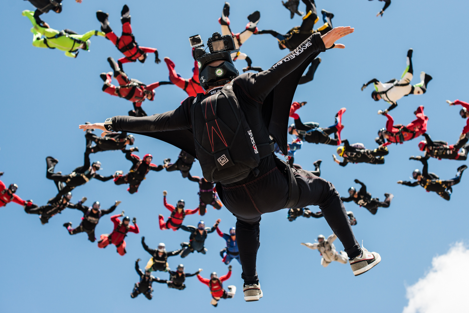 Juan flying on his back below a large formation of skydivers
