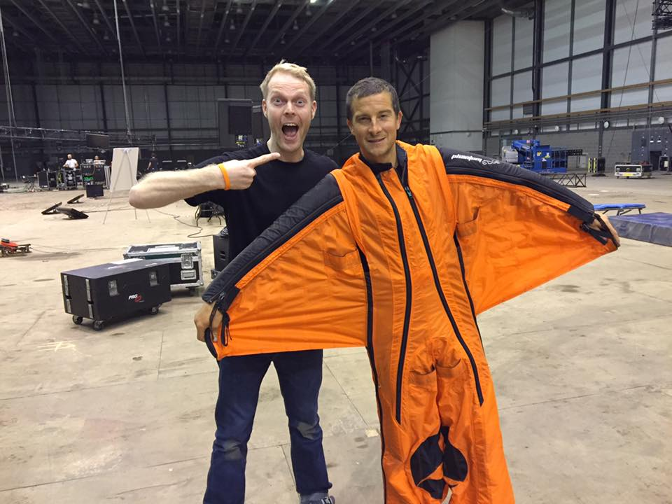 James poses with Bear Grylls who is wearing an orange wingsuit.
