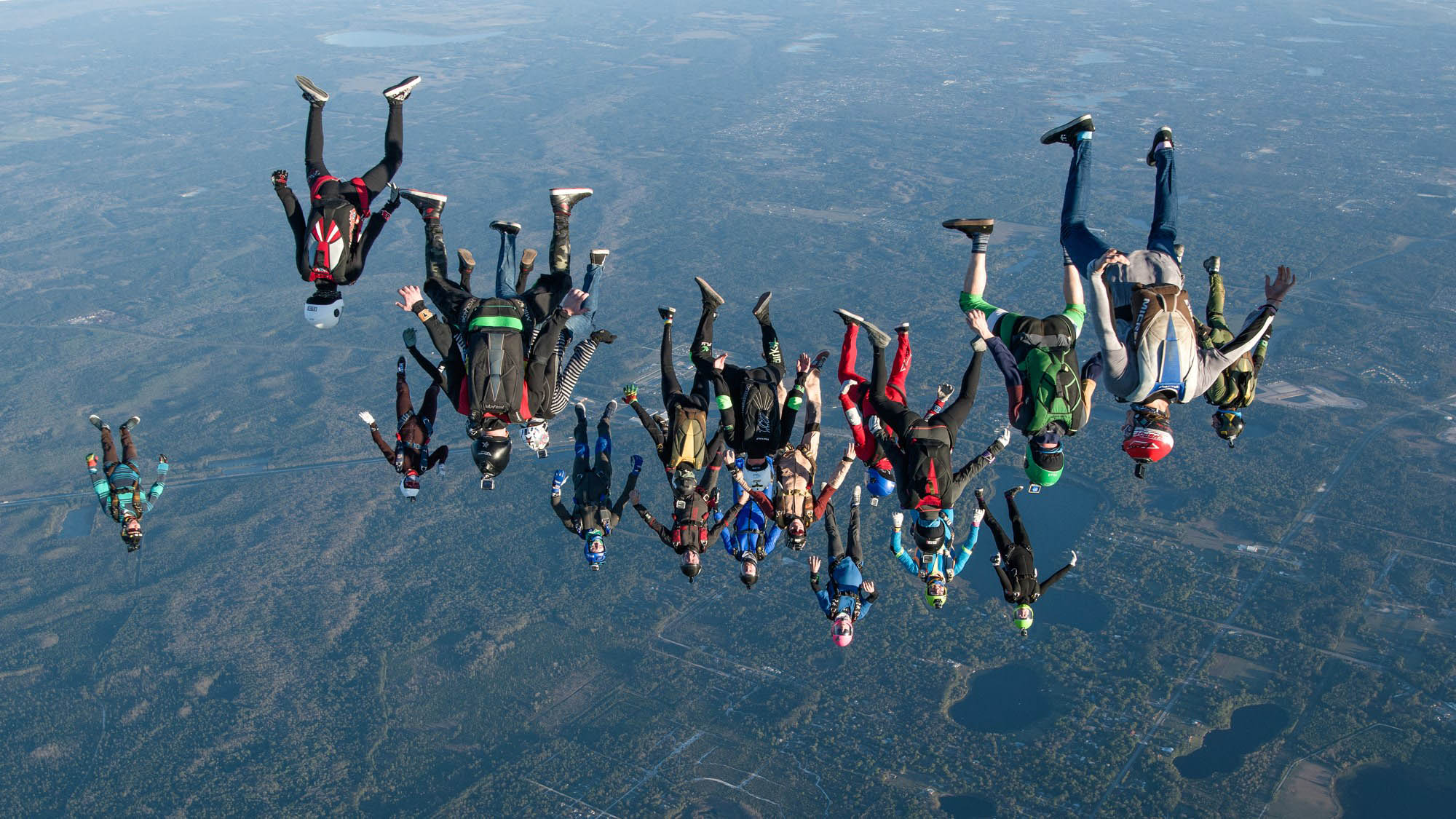 A large group of skydivers flying in a head down position.