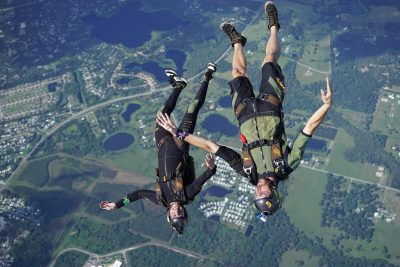 Two jumpers flying in a head to earth position on a skydive.