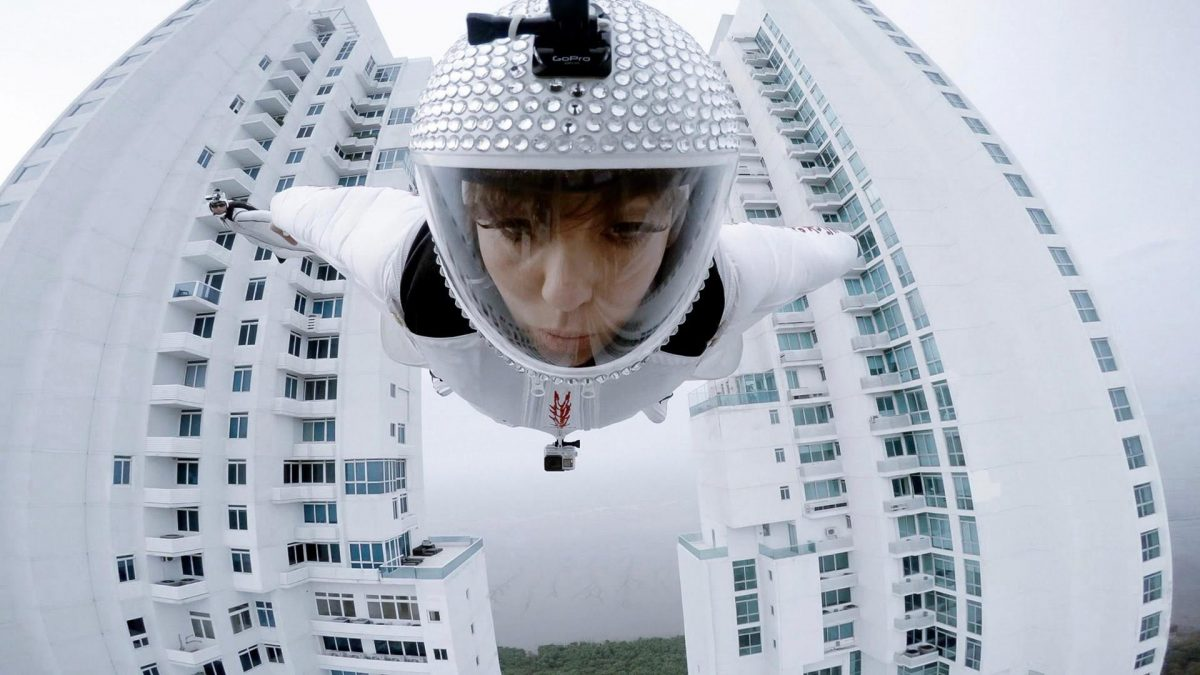 Roberta Mancino flies through two buildings in a white wingsuit.