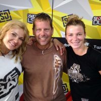 Marcus smiling with two people in front of a Skydive Dubai logoed backdrop.