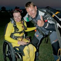 Marcus poses with a tandem student after a jump and gives a thumbs up.