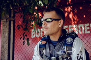 Marcus sitting on a bench in his skydiving gear waiting to board an airplane.