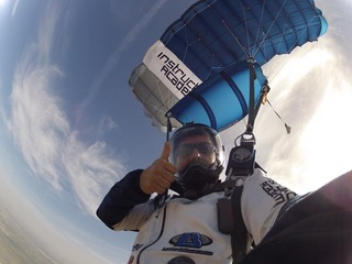 Marcus gives a thumbs up while soaring under parachute.