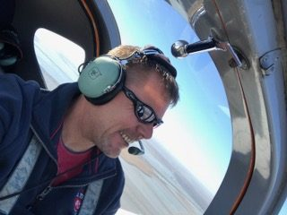 Marcus smiling while piloting an aircraft.