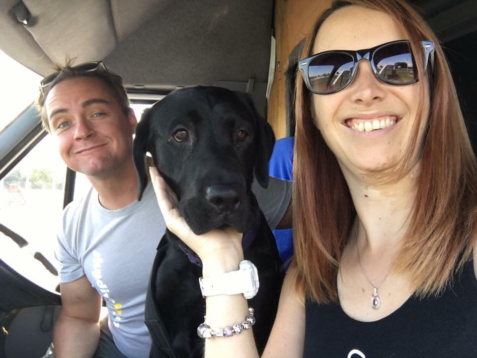 AJ and Mike pose in their camper van with their dog.