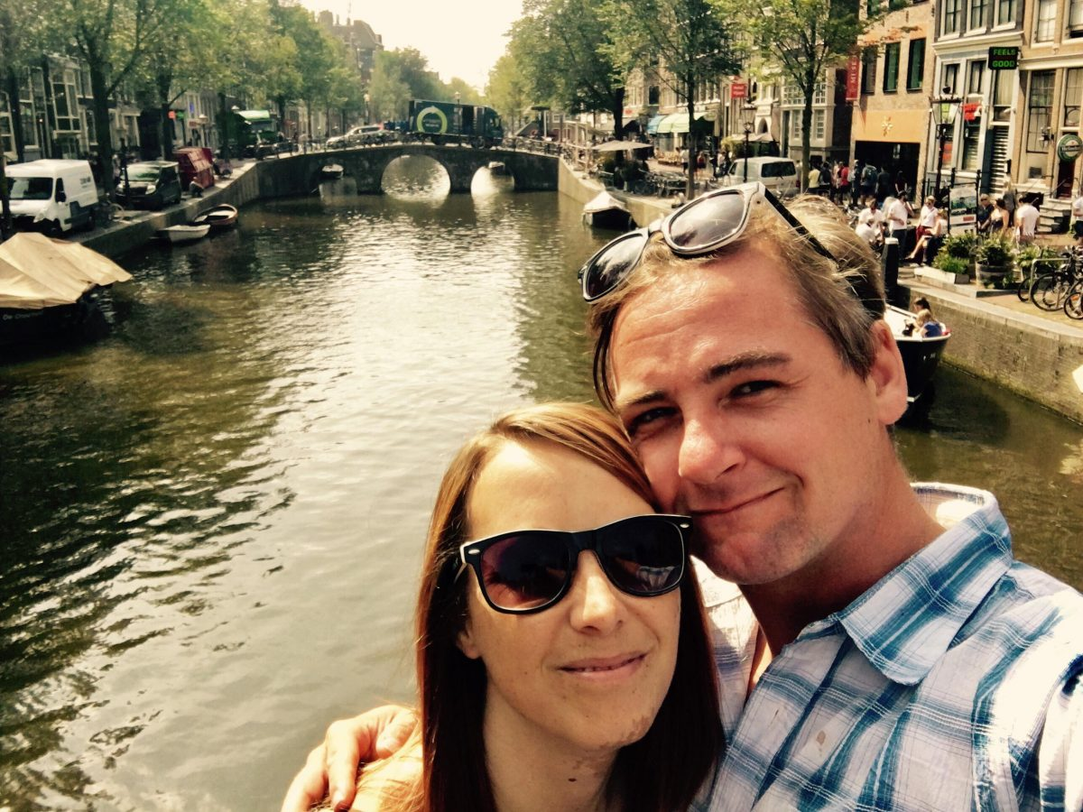 Mike and AJ pose in front of a canal in Amsterdam.