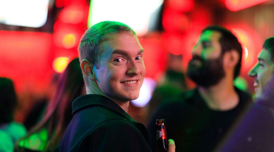 Alex Ogden smiles while drinking a beer at a dropzone party
