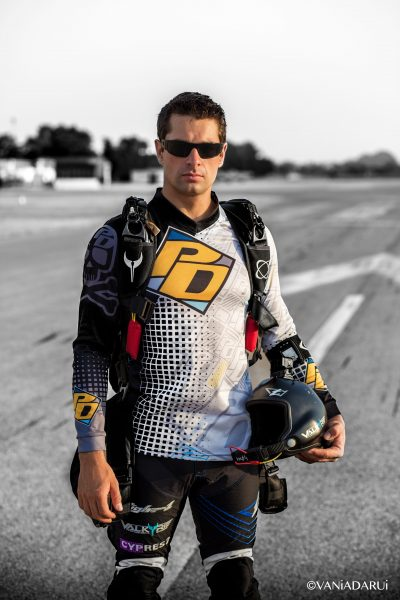 Julien smiles while standing on the runway while wearing his PD sponsored jersey