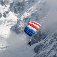Omar flying under a red and blue parachute above a snow filled landscape with Mt. Everest in the background