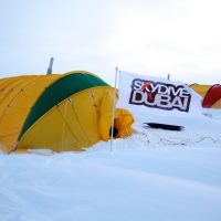 Photo of a yellow tent surrounded by deep snow in the Himalayas