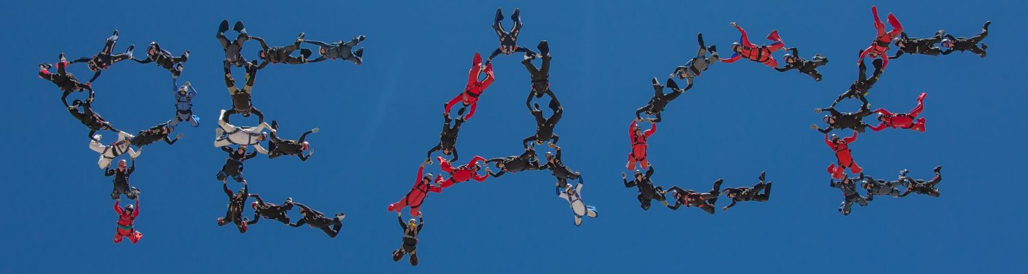 An iconic picture of a group of formation skydivers spelling the word PEACE in the sky