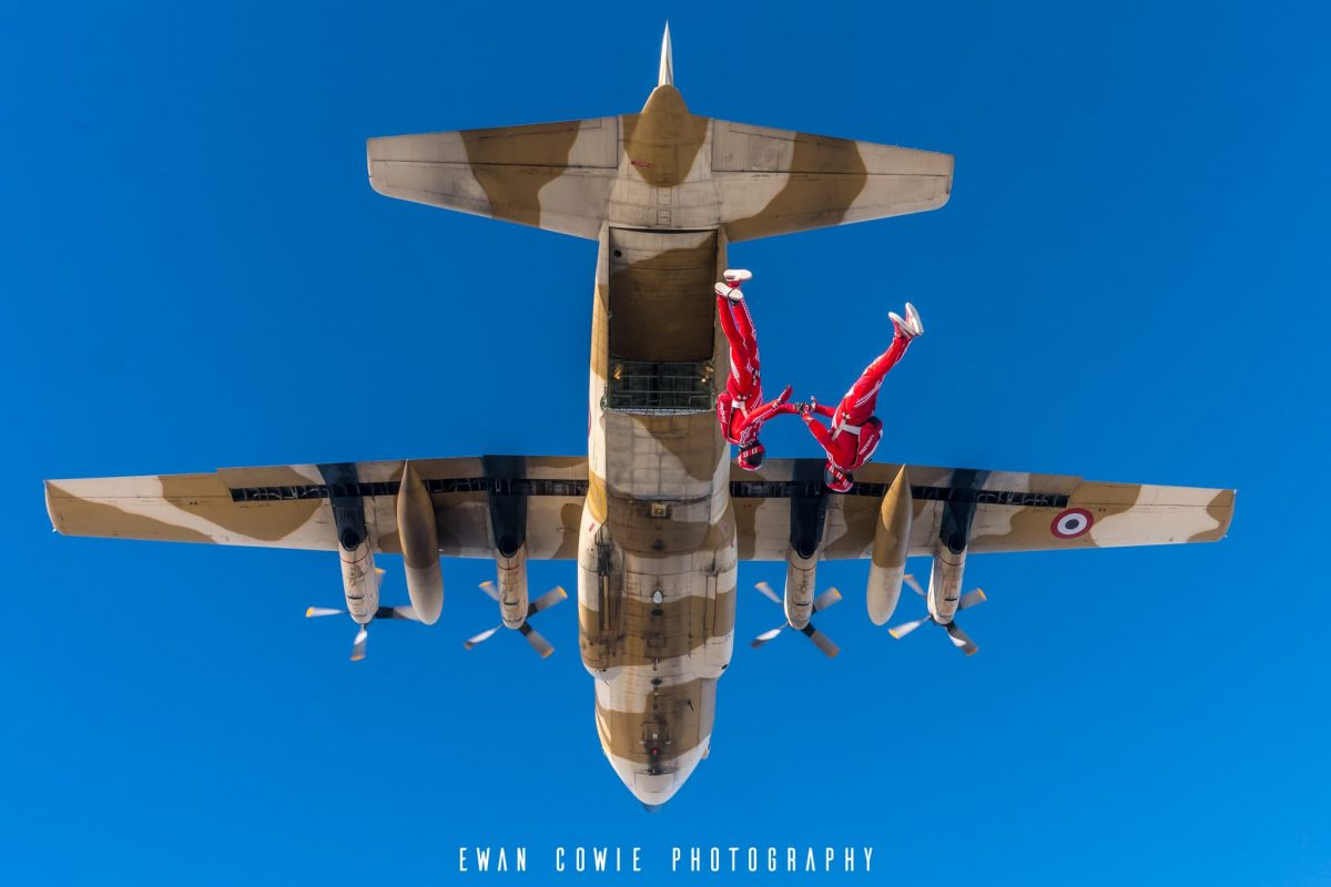 Team Airwax photographed in free fall with a Hercules C-130 in the background