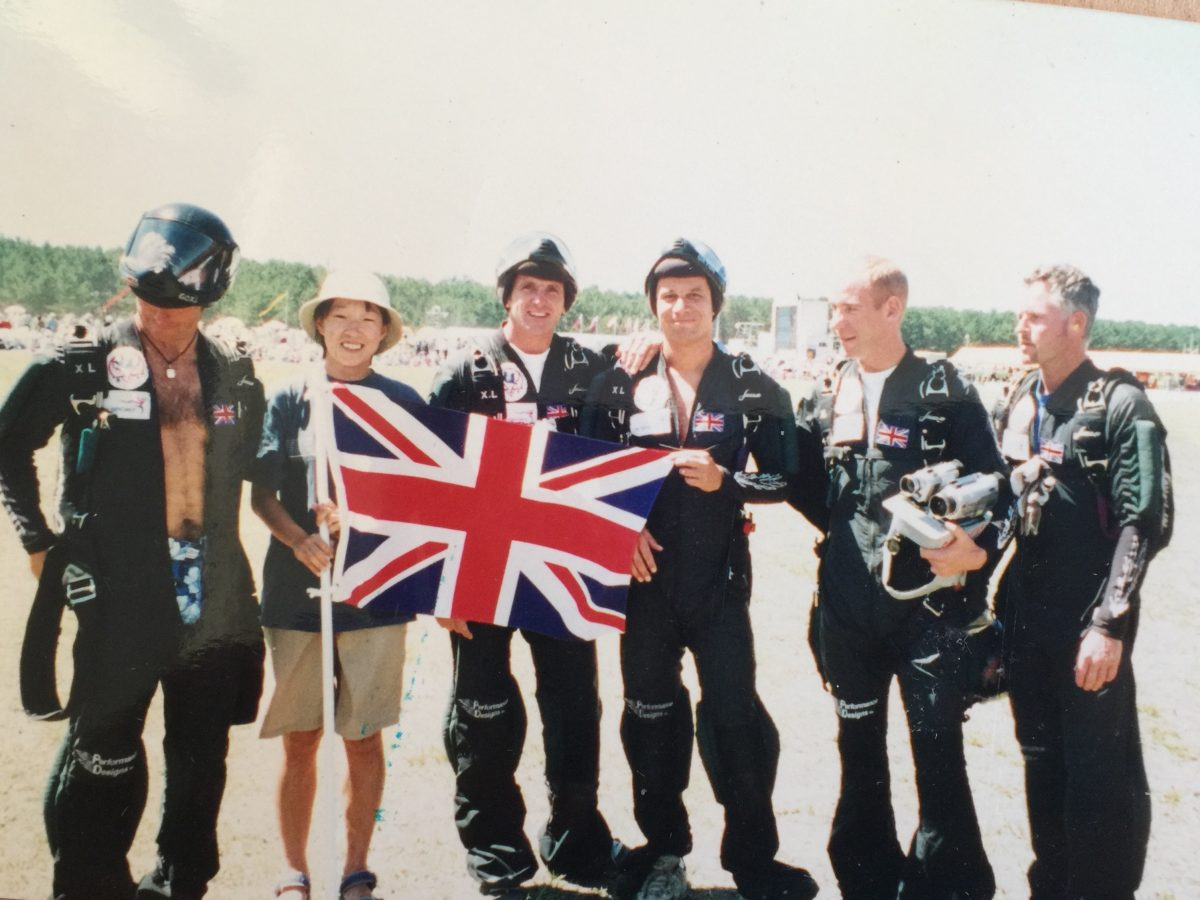 The British Skydiving Team with Pete Allum smiles while wearing their jumpsuits and holding the Union Jack