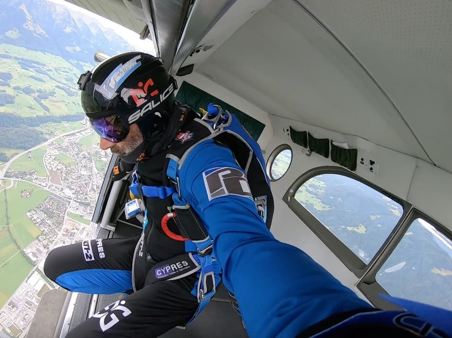 Vito in the door of a plane looking down moments away from jumping.