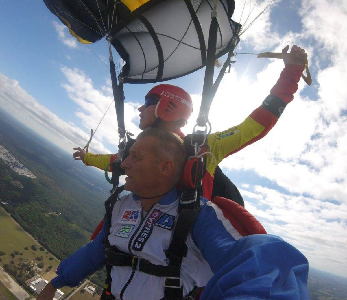 Bram rides as a tandem passenger as one of his students steers the parachute as tandem instructor