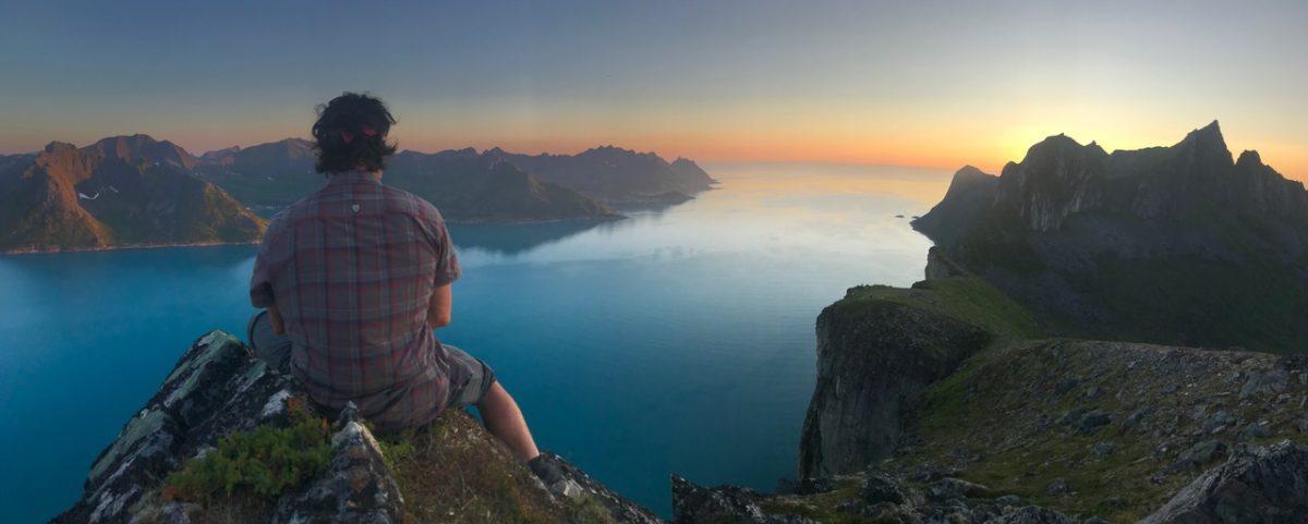 Jason Moledzki ponders life while sitting on a cliff at sunset