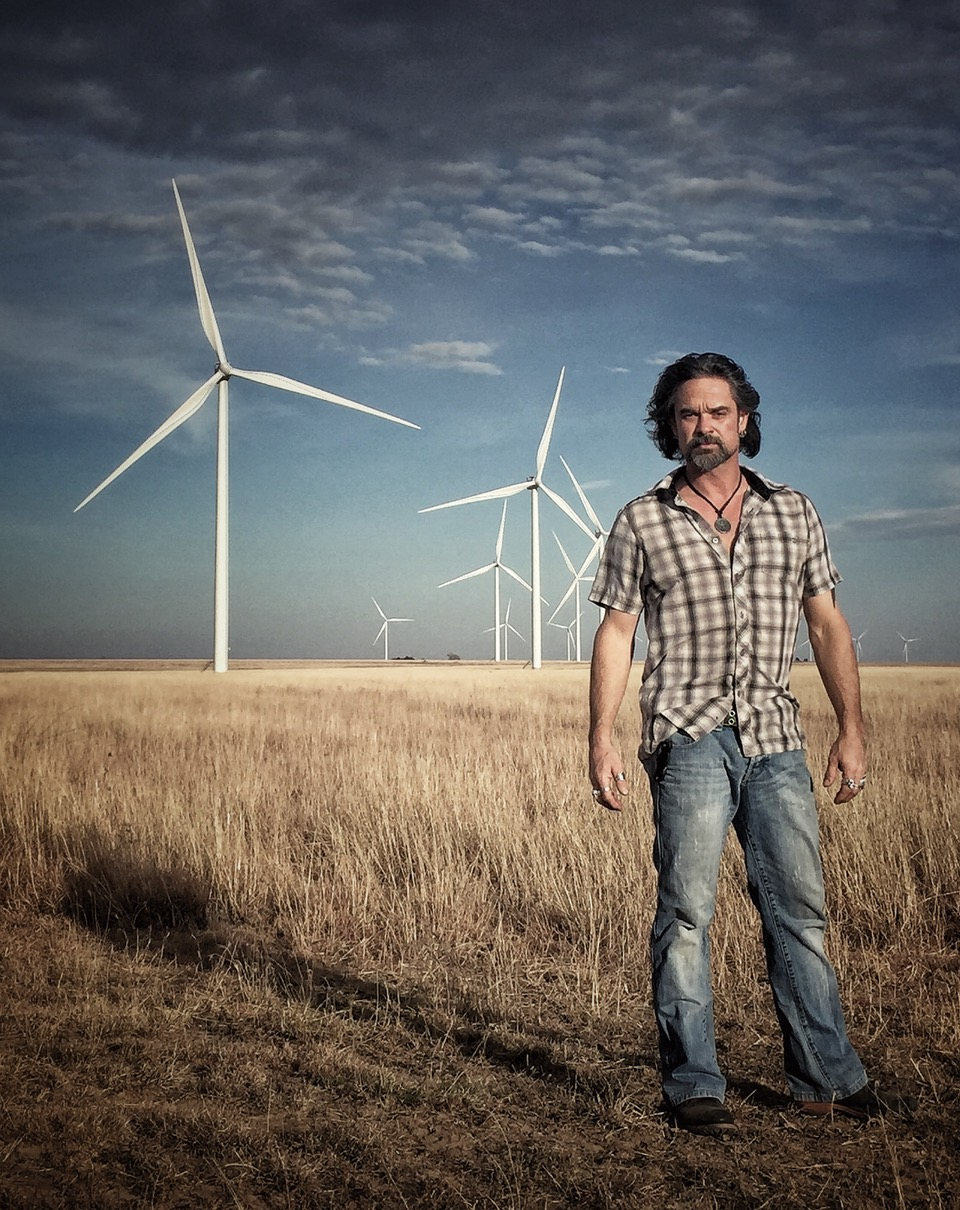 JayMo poses in front of a field of wind turbines