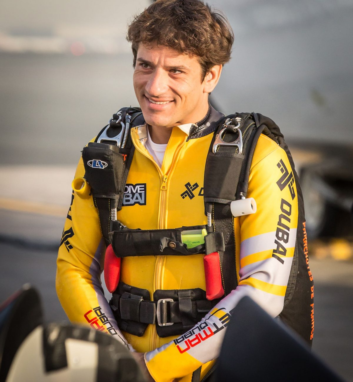 Fred Fugen smiles while wearing a yellow JetMan jumpsuit