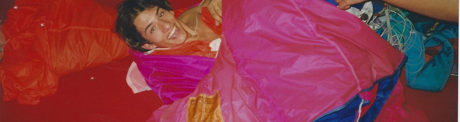 A young Fred Fugen smiles while laying on a parachute on the packing mat